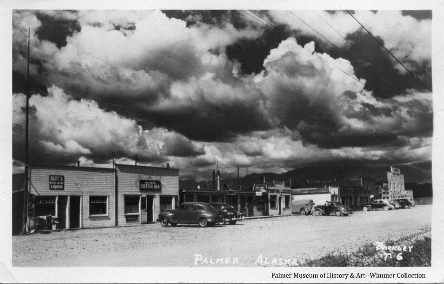 Image is a summer view of Palmer main street with several business buildings and automobiles parked in front. Business signs are apparent, two children and a man are evident, overhead clouds are obvious.