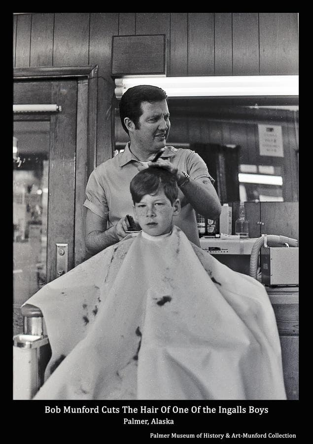 Image is of Bob Munford giving one of the Ingalls boys, thought to be David, a haircut in Bob's Barbershop.