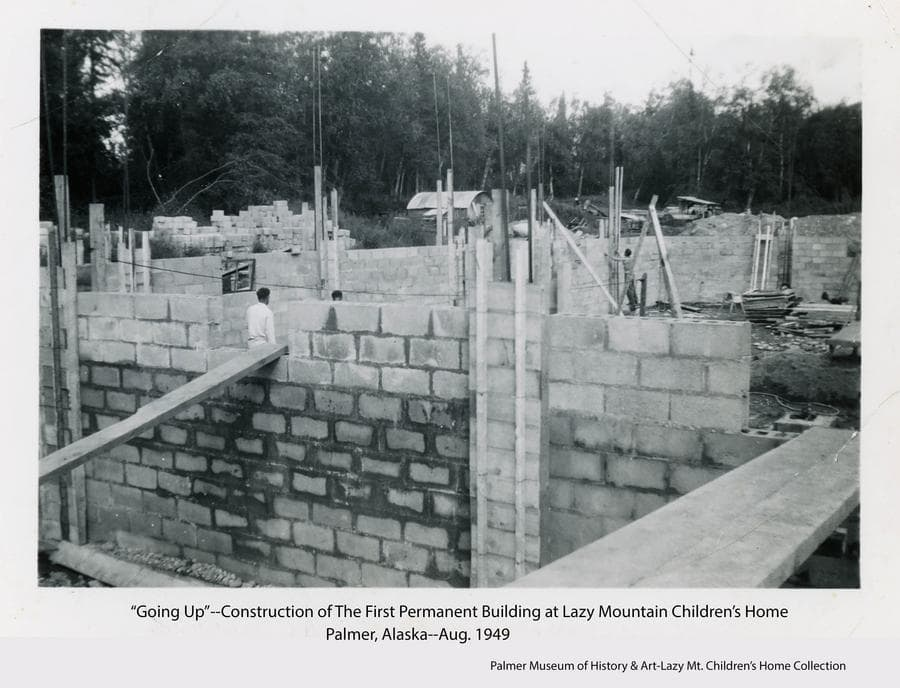 Image shows a concrete block basement under construction for the first permanent building at the Home.  Identified as being a   40' x 90' full basement to house a recreation room, deep freezer, furnace, food storage and more.  Workmen are visible, a Quonset Hut is in far middle ground, heavy forest provides the backdrop.