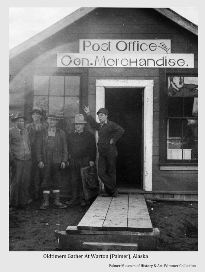 """This is a press photo image of five men, identified as """"Oldtimers"""" of the area, standing in front of a building exhibiting a sign identifying it as a """"Post Office and Gen. Merchandise"""" store.  The story line attached to the photo indicates the men were waiting to welcome the arrival of the Colonists."""