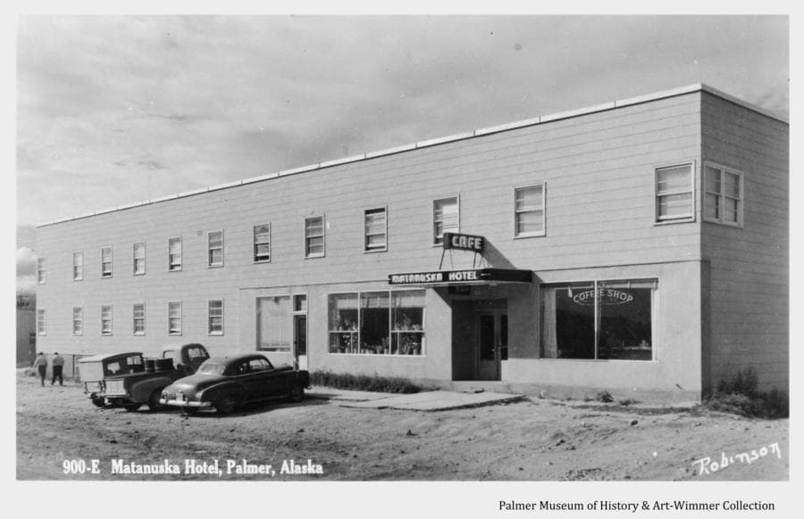 Image is of the two-story Matanuska Hotel and café in downtown Palmer (later re-named the Valley Hotel) as it appeared sometime after it opened in 1948 and before the street in front was paved in 1958.  Three vehicles are parked in front and two men are visible walking away at left.