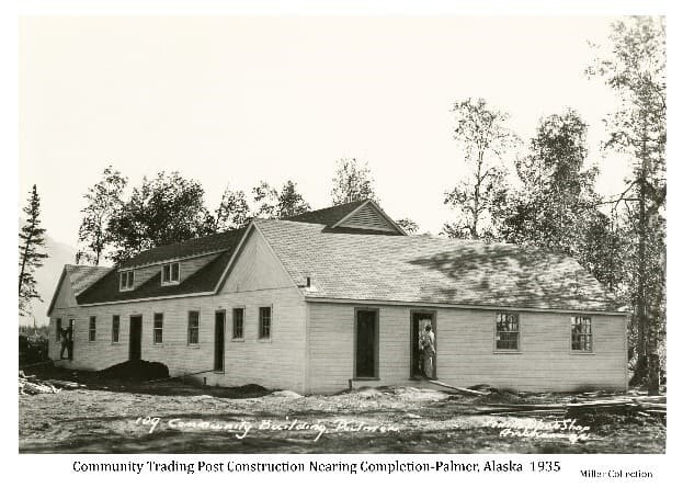 Image is of the Colony Community Trading Post building under construction and nearing completion. View is of the north and west side. Two men are visible working on the building. Trees are behind the building.
