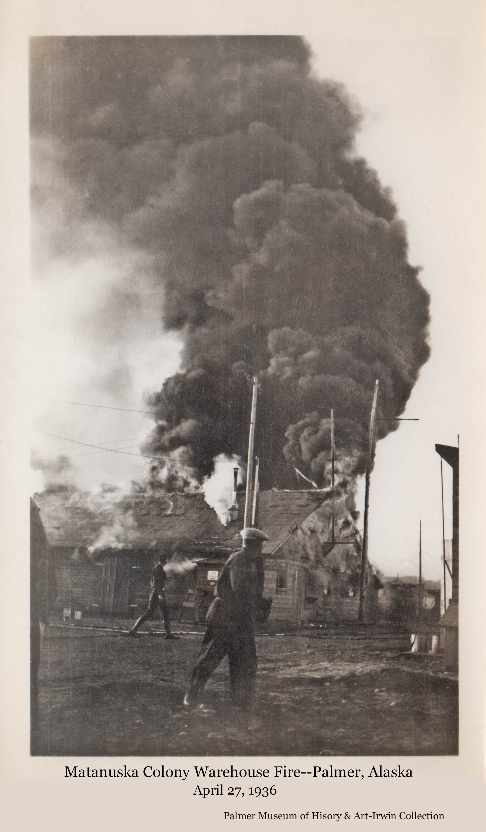 """Image shows heavy dark smoke rising from fire consuming the Colony warehouse in """"Tent City"""".  Men are walking past and observing."""