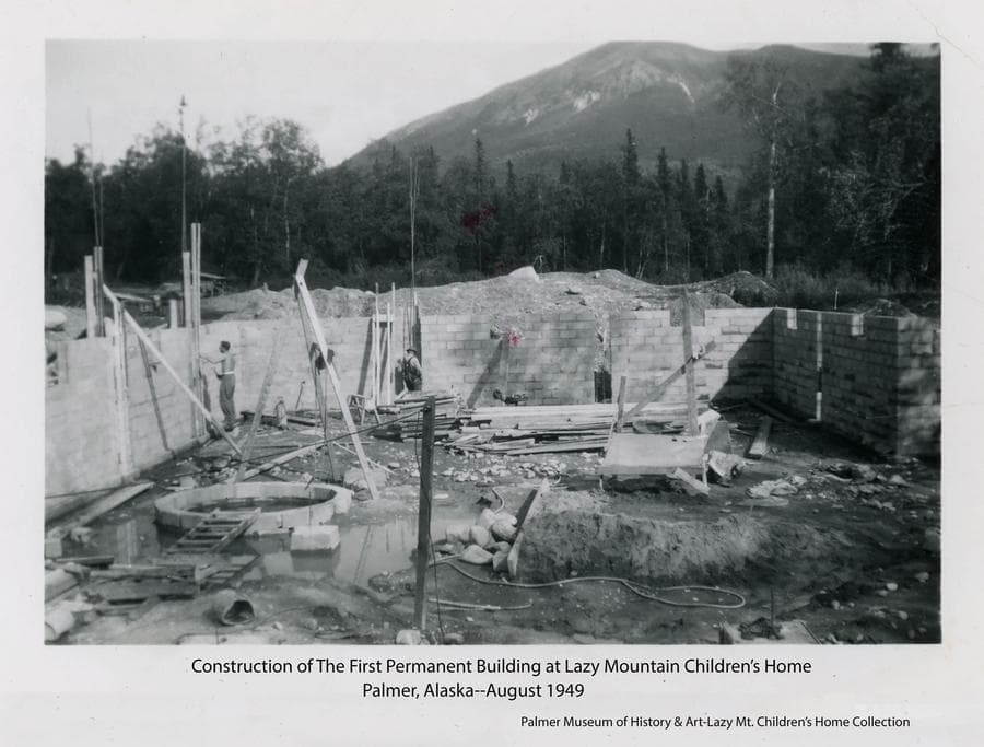 Image shows a concrete block basement under construction for the first permanent building at the Home.  Identified as being a  40' x 90' full basement to house a recreation room, deep freezer, furnace, food storage and more.  The blocked-in well is visible at lower left.  Workmen are visible, heavy forest provides the backdrop with Lazy Mountain in background.