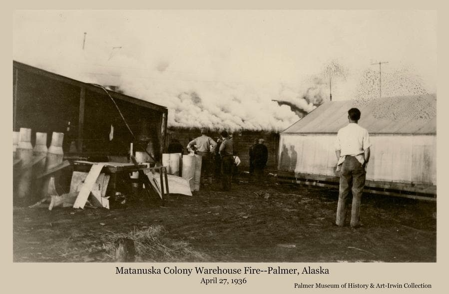"""Image shows heavy white smoke rising from fire consuming the Colony warehouse in """"Tent City"""".  Men are standing and observing.   As well as goods stored in the warehouse, many important records and documents were lost to the fire, causing difficulty for many Colony families in establishing their true indebtedness to the corporation managing the project."""