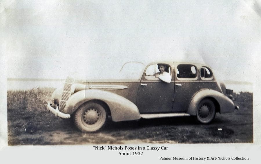 """Image is of Nick Nichols posing in a """"Classy Car"""".  Contemporary photos in our collection support the assumption that this photo was made on a group outing to the Goose Bay area, and the car may have belonged to Grace Bagoy of Anchorage."""