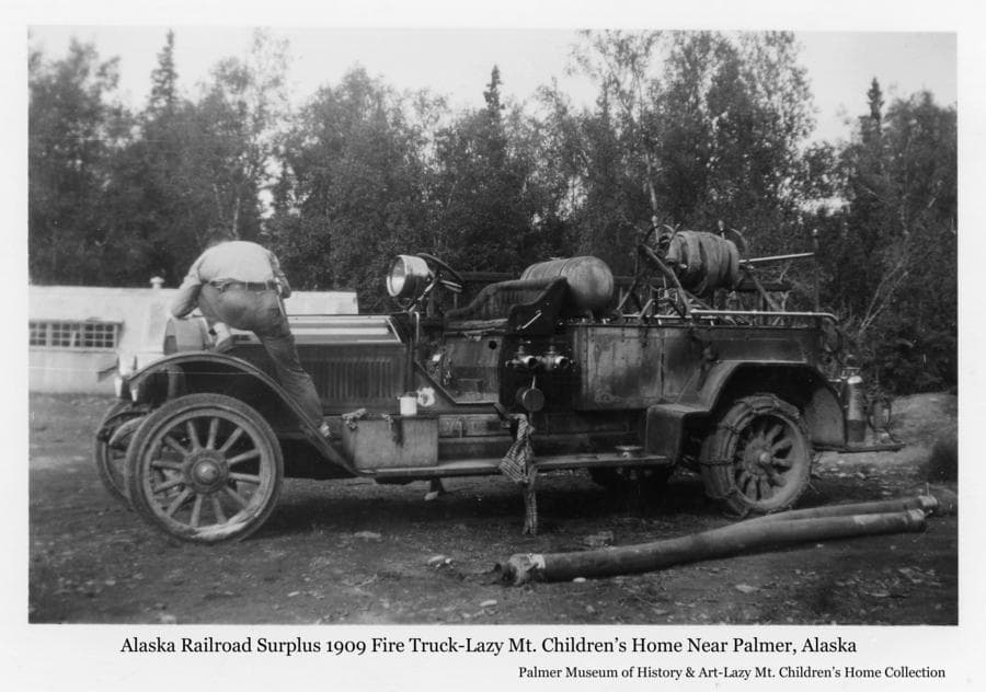 Image is of an old fire truck, identified as Alaska Railroad surplus 1909 vintage, being prepared for service at the Lazy Mt. Children's Home.  A man stands on the front fender attending to the engine compartment.