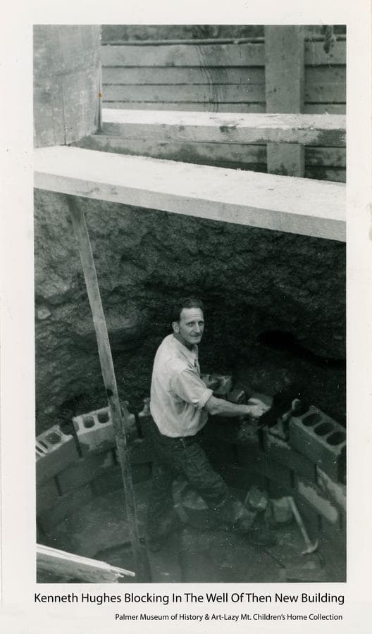Image shows a man, identified as Kenneth Hughes, laying concrete blocks around the well during construction of the first permanent building at the Home.