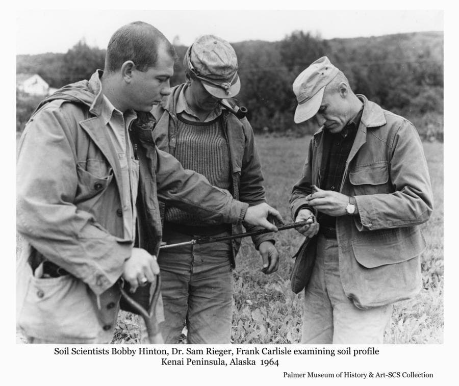 Image shows three men, identified as soil scientists (l to r) Bobby Hinton, Dr. Sam Rieger, and Frank Carlisle, inspecting a soil sample drawn from the ground by a soils probe tool.  Headquartered in Palmer, they were reviewing soils surveyed and mapped on the Kenai Peninsula. The soil survey is the basic tool of land-use planning in Alaska.  SCS technicians use the survey to advise homesteaders on which land is most suitable to clear and the best use for each soil type on the homestead.