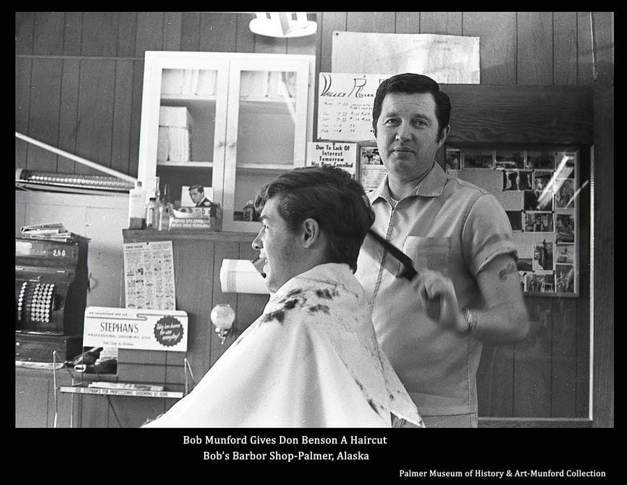 """""""Barber Bob"""" Munford is seen giving a haircut to local young man, Don Benson, in Bob's Barber shop.  The cash register shows a value of $2.50 rung up with the last transaction which might give an indication of the price of a haircut at the time."""