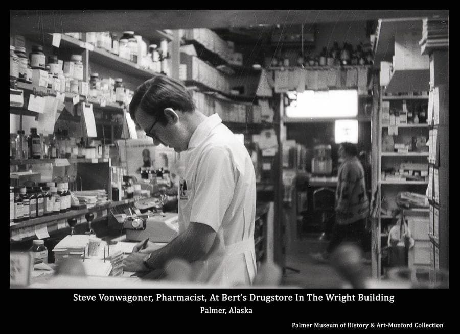 Image is of Steve Vonwagoner, pharmacist at Bert's Drugstore, working at the counter in the pharmacy.  Visible through the doorway behind, an unidentified woman walks past the drugstore soda counter.