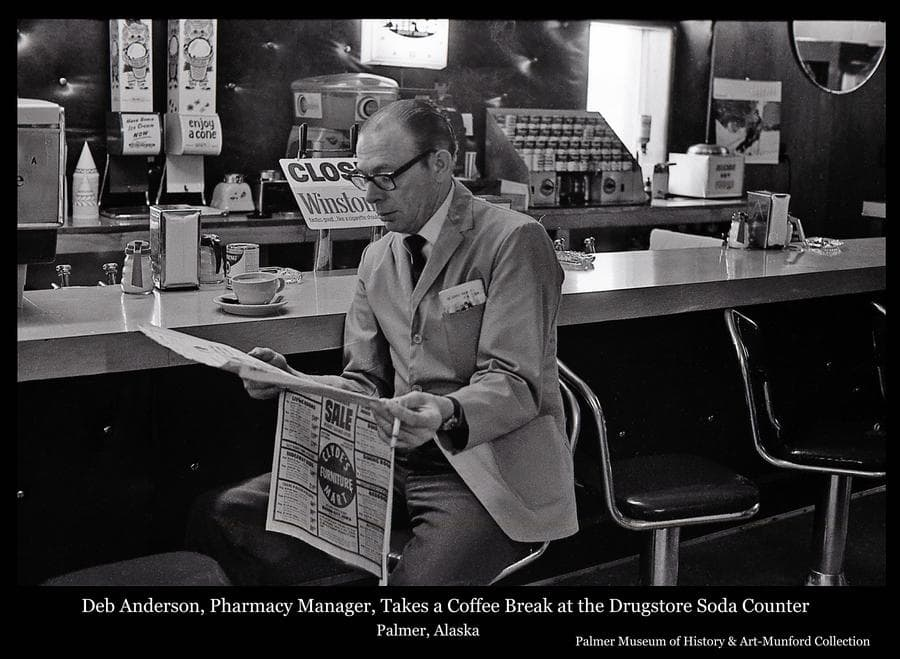 """Image is of Delbert (Deb) Anderson, manager of the pharmacy in Bert's Drugstore in Palmer.  He is seen here taking a coffee break at the Drugstore soda fountain/lunch counter.  """"Lunch"""" service generally focused on the """"Campbell's Soup Counter Top Kitchen"""" visible over Deb's shoulder.  The customer would select from a variety of Campbell soups available and the can would be emptied into a stainless steel mug with electric heating coils in its walls.  The heating element projecting from the side of the mug would be plugged into the counter-top cabinet seen here, the timer would be set, and in due course hot soup would be served for lunch."""