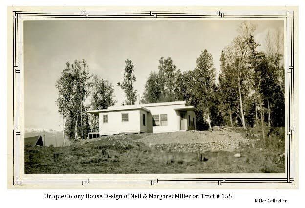 Image shows a white, flat-roofed house on a small hill with exposed excavated gravel in front and trees behind. Designed by Colonists Neil & Margaret Miller to be distinctively different from other Colony houses, to the consternation of ARRC officials. Part of another building is visible behind and to the left of the house with snow-capped Talkeetna Mountains in the background.