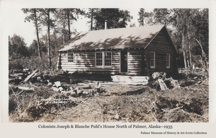 Image is of the log home of Colonists Joseph and Blanche Puhl located a half mile north of Palmer on tract #99.  Exterior is complete.  Lumber, wood, stumps and brush in the yard.  Birch trees behind.