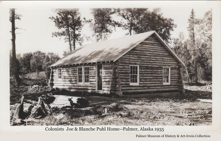 Image is of the log home of Colonists Joseph and Blanche Puhl located a half mile north of Palmer on tract #99.  Exterior is complete.  Lumber and stumps in the yard.  Birch trees behind.
