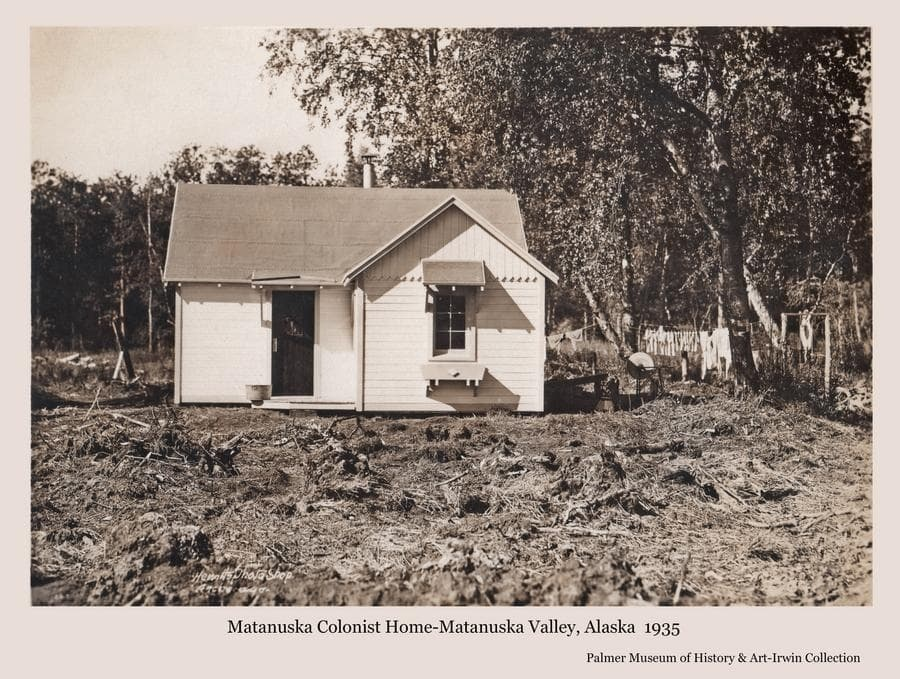 """Image is of a completed Colony """"Cottage"""".  A grindstone and washing hanging on a line are visible at right.  Birch forest is the backdrop."""