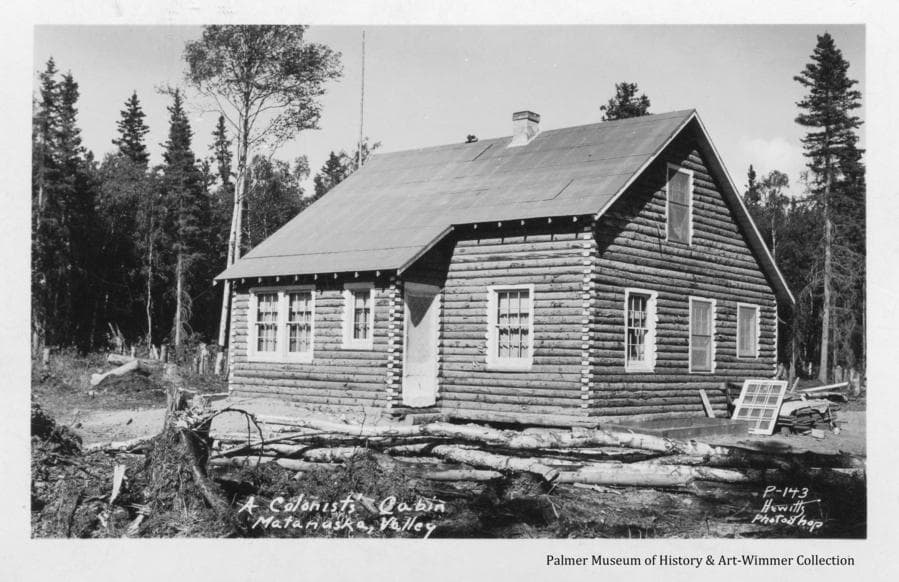Image is of a Colony log home in middle ground, stumps and logs in foreground.  Windows and other material stacked alongside the house.  Exterior construction is essentially complete.  Heavy forest beyond.