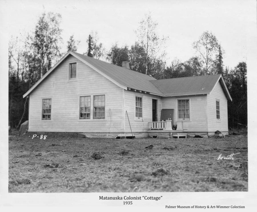 """Image is of a white frame house (or """"Cottage"""" as the Government termed it) constructed for a Matanuska Colony family.  The yard has been cleaned up of construction material and banking of earth around the foundation has begun.  Birch and spruce forest forms the backdrop."""