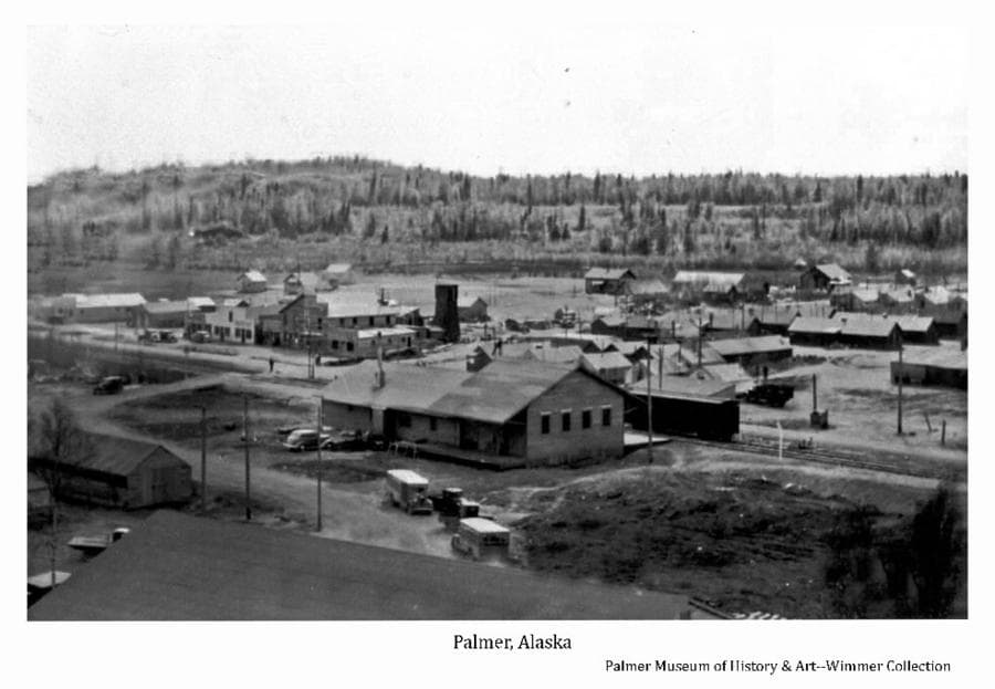 """Image is a summer low oblique view across the Co-op garage, including the Railroad depot at center with a railroad car adjacent, the south end of Palmer business district, buses in foreground, numerous small buildings, fields, hill and forest beyond. Companion photo with """"Palmer Business Section #1""""."""