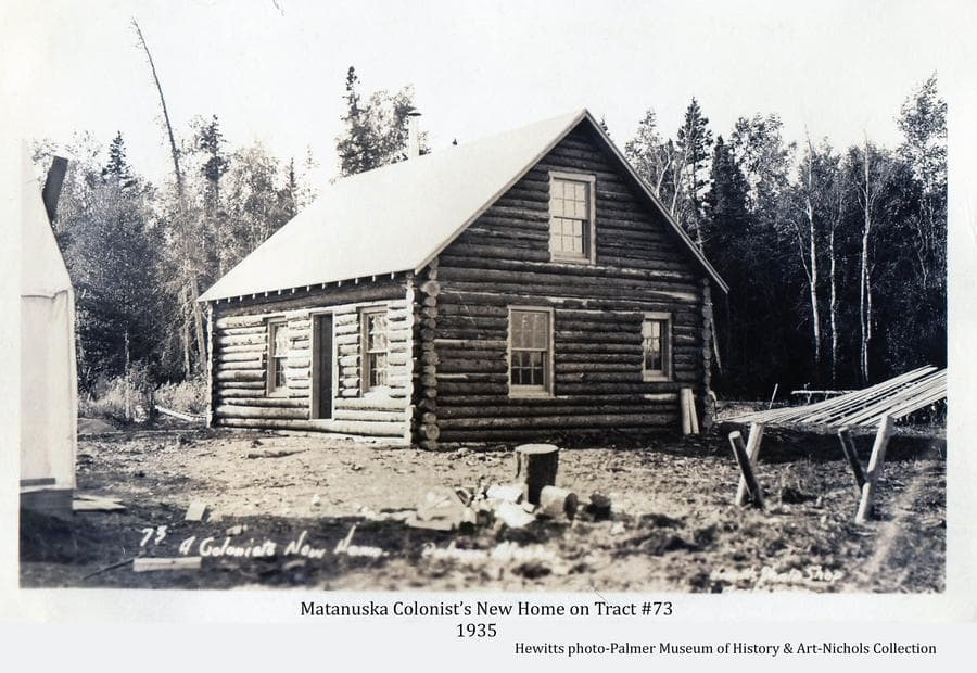 Image is dominated by a log Colony house with exterior construction essentially complete.  A colony tent is partially visible at left, lumber arranged at right with chopping block and sawbuck in foreground.  Heavy forest behind.