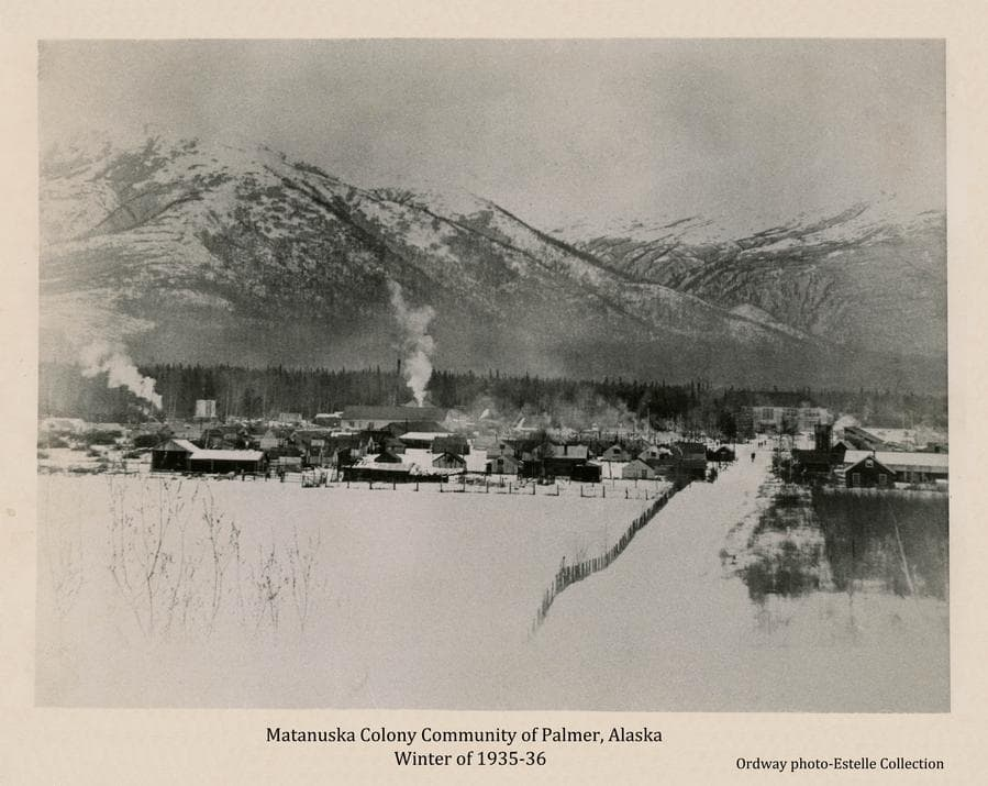 """Image shows an easterly winter view of Palmer taken from Bugge's hill.  John Bugge's homestead field is in foreground with fence along the """"Wasilla road"""". Buildings are evident in middle ground and people can be seen walking in the street.  Scaffolding is still in place on the school building and the water tower is not yet erected.  Steam rises from the power house and white smoke comes from a railroad engine.  A strip of forest is in far middle ground and mountains dominate beyond."""