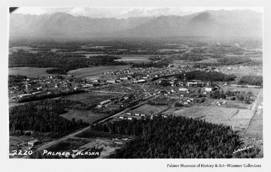 Image is an aerial oblique looking northwest across the city of Palmer, including farms, fields, forest, roads and Talkeetna Mountains in background. The State Fair is apparently open as many parked cars and people are visible at the fairgrounds.
