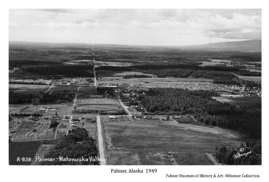 Image is an aerial oblique looking west across the city of Palmer, including farms, fields, forest, roads and west end of Talkeetna Mountains in background. Buildings and roads are evident.