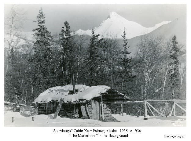 """Image is a winter scene of a log cabin in foreground with snow on the ground and roof. A rail frame fence is adjacent with mixed birch and spruce forest behind. Mountains form the near backdrop with a conical peak prominent, variously identified over the years as """"The Matterhorn"""", Beyers Peak, and Matanuska Peak.  Other photos in the collection indicate the fenced area was probably fox pens.  An associated cache was located in front of the cabin closer to the Matanuska River,  The road that developed between Palmer and the Bodenburg Butte area passed between the cabin and cache.  The cabin is believed to have belonged to Eugene Marsh."""