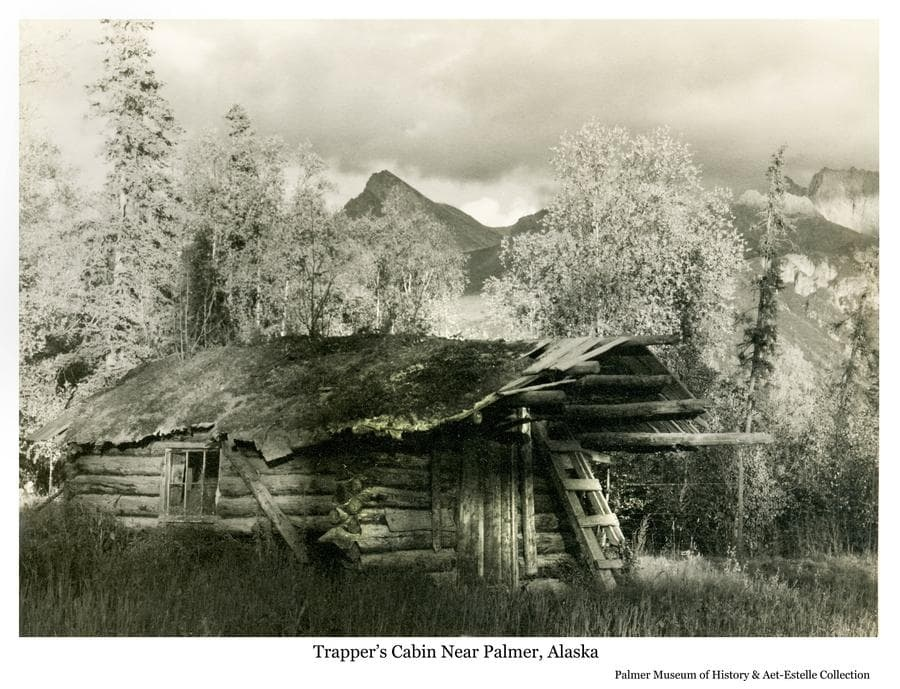 """Image is a summer view of a log trapper's cabin located on the north side of Matanuska River east of Palmer.  The mountain beyond has been known variously as """"The Matterhorn"""", """"Beyers Peak"""", and """"Matanuska Peak"""".  The cabin is thought to have belonged at one time to Eugene Marsh."""