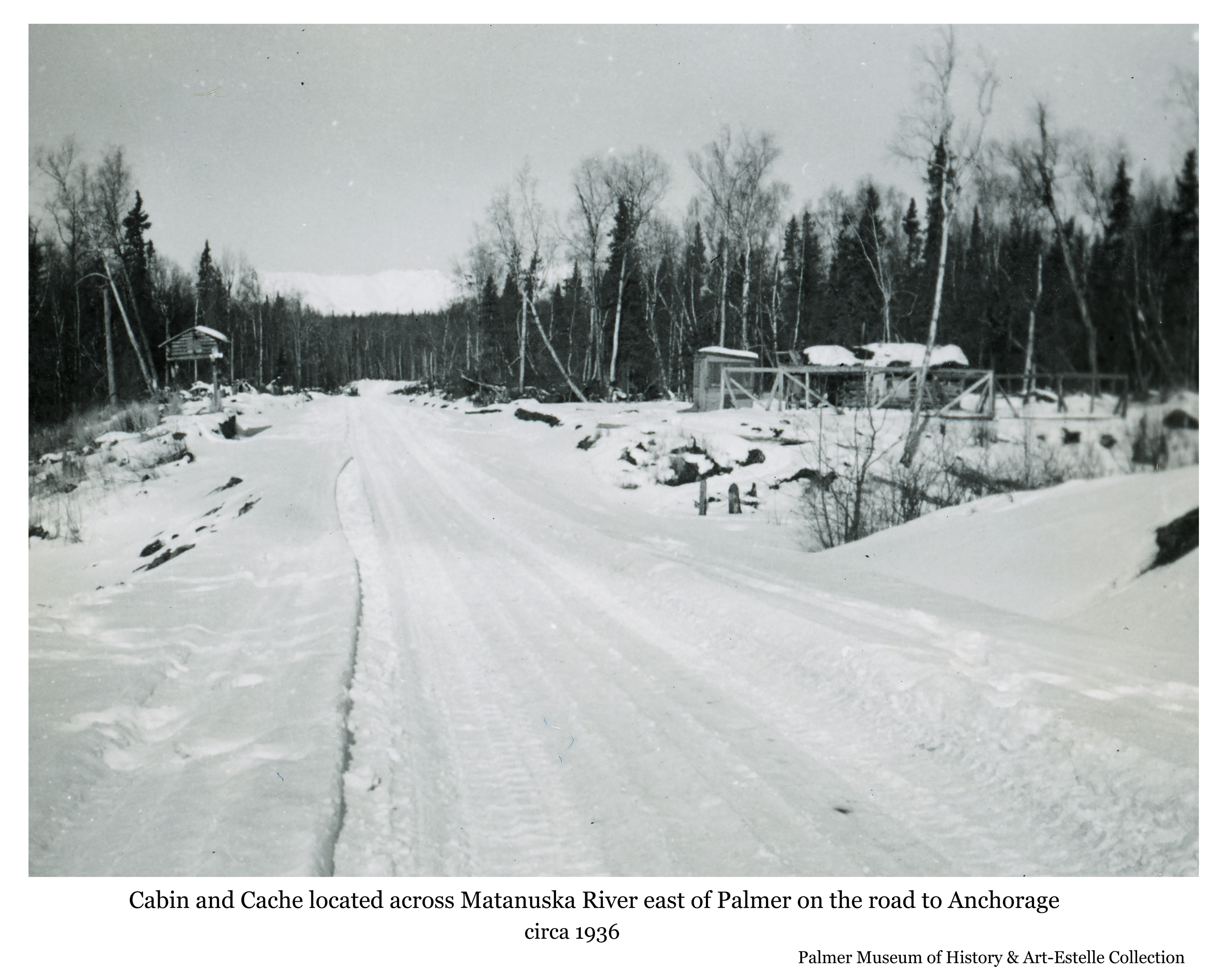 Image is a winter view looking north along the snow-covered Palmer to Anchorage road about a mile east of the Matanuska River bridge.  Shown is a log cabin, fox pens, and another small structure on the north side of the road and a cache on the south side.  Heavy birch and spruce forest is the backdrop of the clearing with snow-covered Talkeetna Mountains visible in background beyond the cleared roadway.
