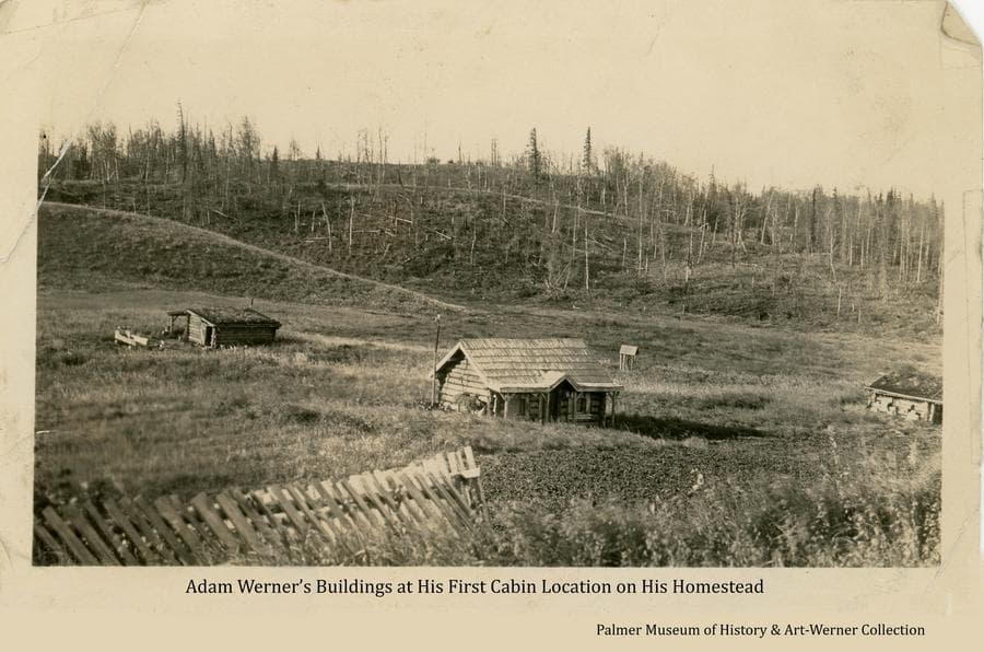 """Image shows a wood slat fence in foreground, a strawberry patch, a log house, well, and two other log buildings in a large clearing with partly cleared forest on hills beyond.  Note on the reverse: """"Adams first house, 1914, when he homesteaded, where his cat could open the door.  There were more small wild animals around then up until about 1925.  He moved up here [to the present home location] because the wind blew to much down his chimney & snow drifty to much getting out to the road or trail he made. Eventually became a strawberry patch. Torn down 1931, some [logs and other material] brought up here."""""""