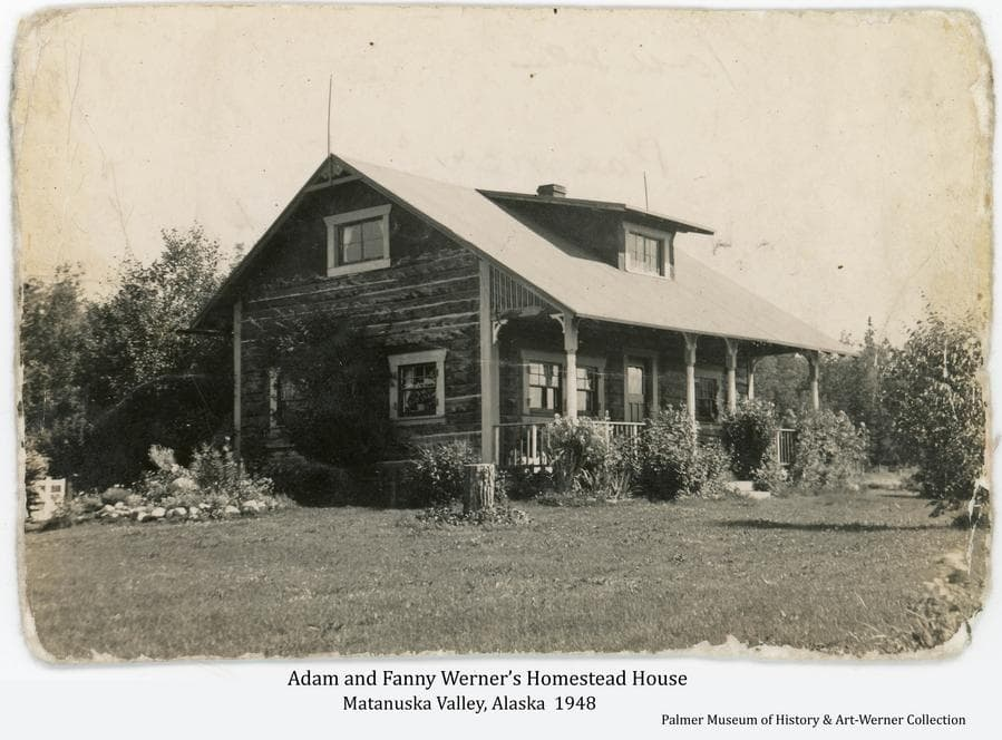 """Image shows the permanent log house Adam Werner built """"up the hill"""" from his first cabin site.  It took four years to build while developing other aspects of the homestead.  Seen here with maturing landscape shrubs and flowers under the care of Adam's wife, Fanny."""