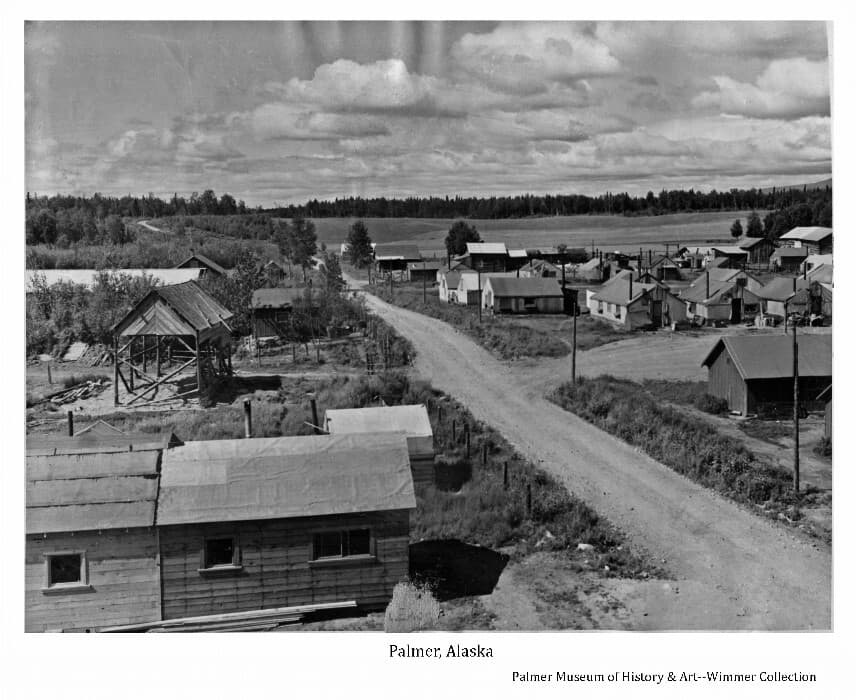 """Image is a west-facing view of tents and small buildings, some that served the Matanuska Colonists at Palmer during the early summer of 1935, some part of John Bugge's homestead and other adjacent homesteads. The """"Wasilla Road"""", as it was called in Palmer, is prominent in foreground. A pole barn is evident in foreground, Bugge's hay barn is visible in middle ground. Bugge's fields are evident in background with forest beyond."""