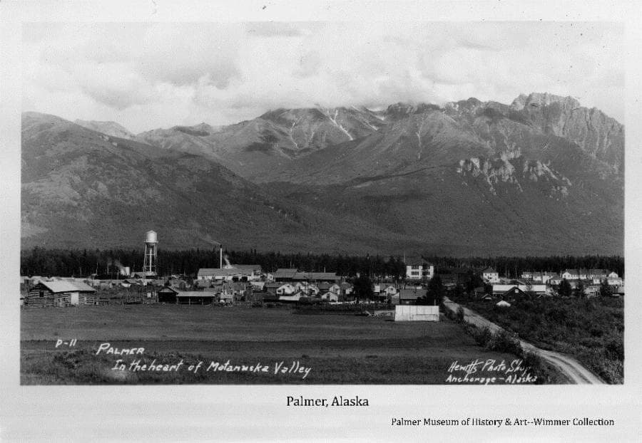 Image is a summer view of Palmer buildings in middle ground, a field in foreground, forest and mountains prominent in background. Homesteader John Bugge's homestead buildings are evident as is the Palmer-Wasilla road.