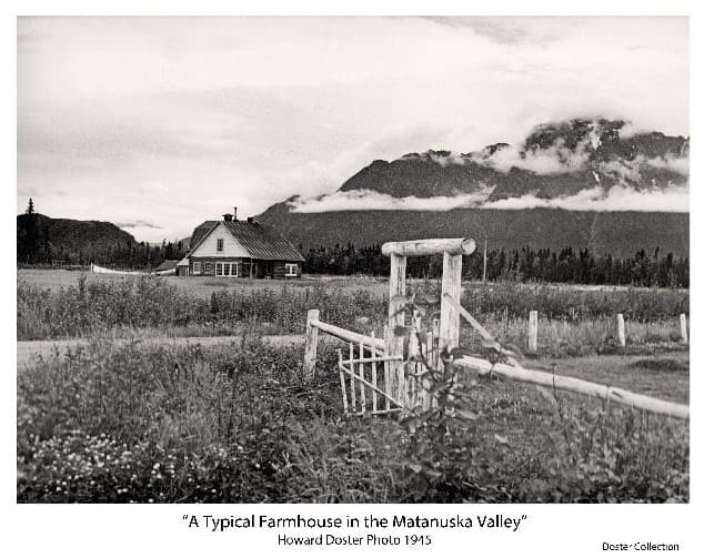 Image is of a log house in the middle ground with a typical Colony barn partially visible behind. In foreground is a fence with a log arch and rails adjacent to a gravel road. Bodenburg Butte is visible in the background as is Pioneer Peak with adjacent clouds.