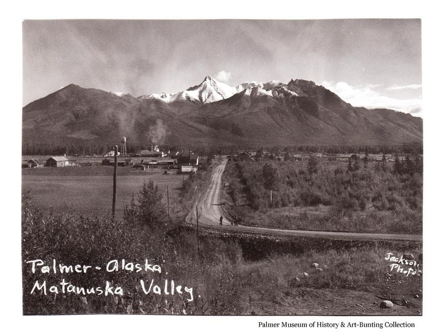 """Image is an early fall easterly view of Palmer as seen from Bugge's Hill, looking down the """"Wasilla Road"""".  People are evident walking on the road in foreground.  John Bugge's homestead field and buildings are in middle ground.  Palmer buildings are in far middle ground.  Mountains with early snow are in background."""