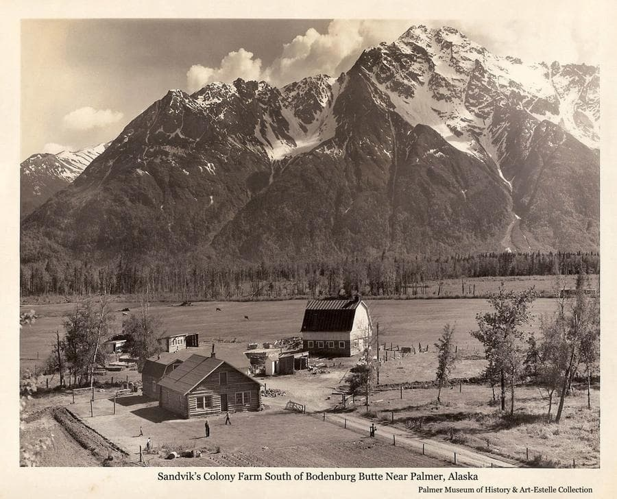 Image is a low oblique summer view of Ingolf and Agnes Sandvik's Colony farmstead at the base of Bodenburg Butte south of Palmer.   People are visible in the yard.  Pioneer Peak, with remnant snow at elevation, forms the backdrop.
