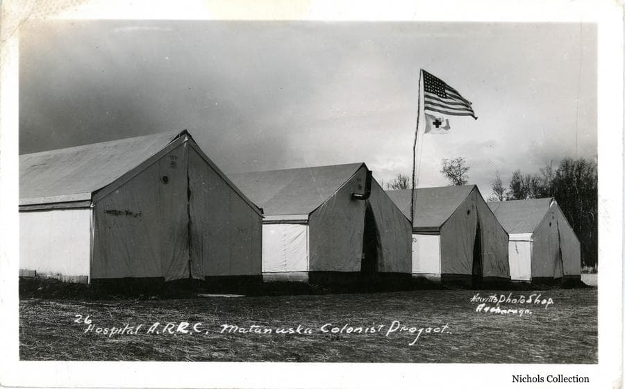 Image is a view of four tents with an American flag and a Red Cross flag flying on a pole overhead, identified as the Colony hospital tent complex.
