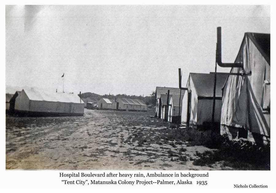 """Image is a view down a dirt street showing tents and two frame structures on the right in foreground and tents at left in middle ground.  Large tents in center are medical facilities.  The colony ambulance and """"nurses car"""" is visible in front of one of the hospital tents.  The American flag is visible on a pole over the complex."""