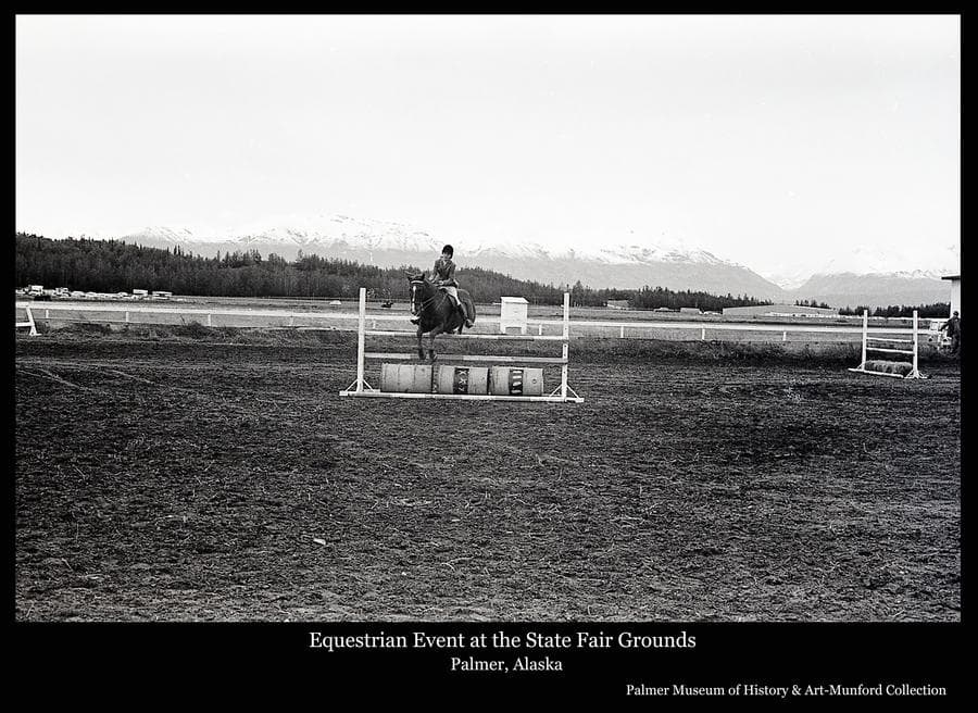 Image is of a horse and rider jumping over a hurdle bar at the State Fairgrounds in Palmer.  Talkeetna Mountains, capped with snow, are in background.