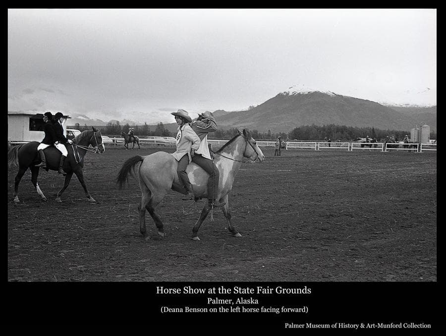 Image is of horses with two riders in the arena at the State Fairgrounds in Palmer.  People, horses and vehicles are evident outside the arena fence.  Chugach Mountains, capped with snow, are in background.  Rider facing forward on the horse at left is identified as Deana Benson.