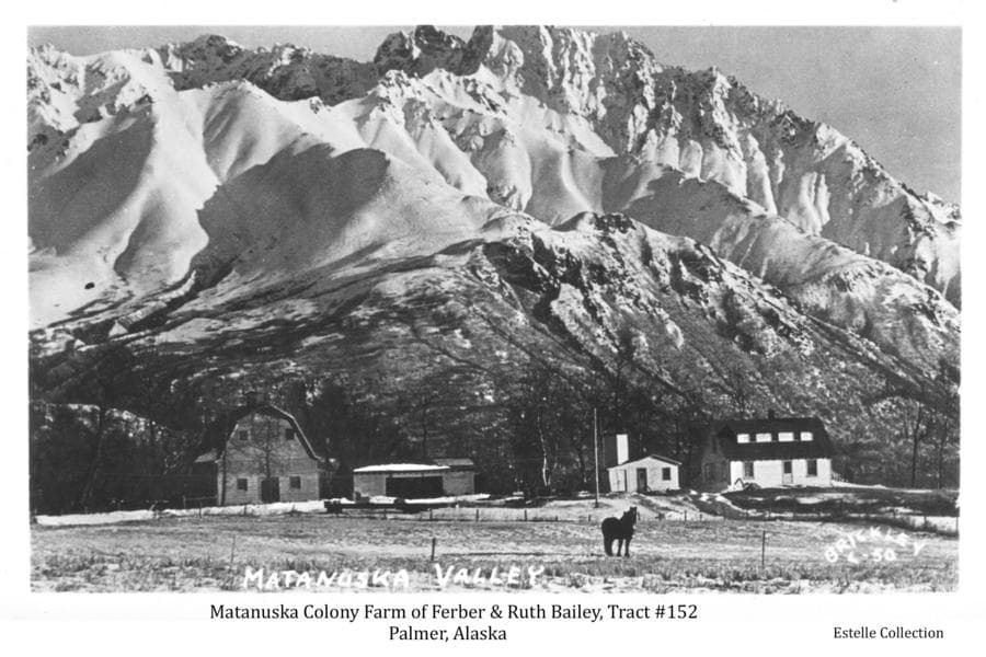 Image is an easterly winter view of a horse standing in a field in foreground, a colony house, barn and other buildings in middle ground and prominent snow-clad mountains beyond.