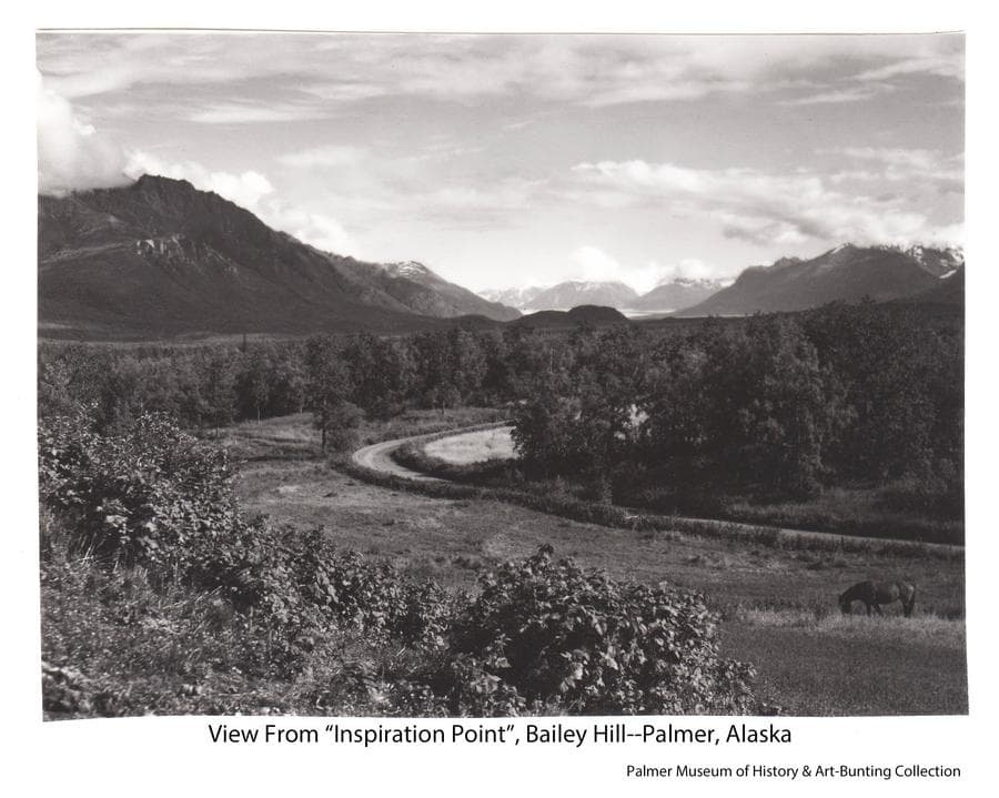 """Image is a southeasterly view from Bailey Hill, north of Palmer, toward the Knik River valley.  The Knik Glacier is visible in the background with mountains on both sides.  Middle ground is heavy forest.  In foreground is a small field and a road section showing the curve in alignment necessary to ascend Bailey Hill, ultimately arriving at the point from which this photo was taken.  This was the only point on the road providing this expansive view of the Valley, thus the local name """"Inspiration Point"""", and a popular stop for photographs. The road, which ultimately became Glenn Highway, was later straightened to cut through Bailey Hill, eliminating this section.  A horse is apparent in foreground."""