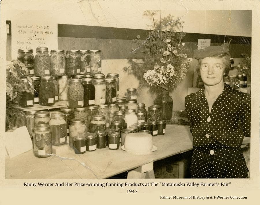 """Note typed on the reverse: """"Prize winning exhibit of canned products displayed by Mrs. Adam Werner, Palmer, Alaska at the Matanuska Valley Farmer's Fair, August 30-31 and September 1, 1947.  Mrs. Werner, a resident of Palmer since 1929 and mother of three 4-H members, displayed 43 quarts homegrown food including beef, sheep, sausage, fish, vegetables, berries, apples, jellies, mushrooms, dried herbs, butter, milk, cheese and vegetable confections.  Her garden contains 18 varieties of herbs."""""""