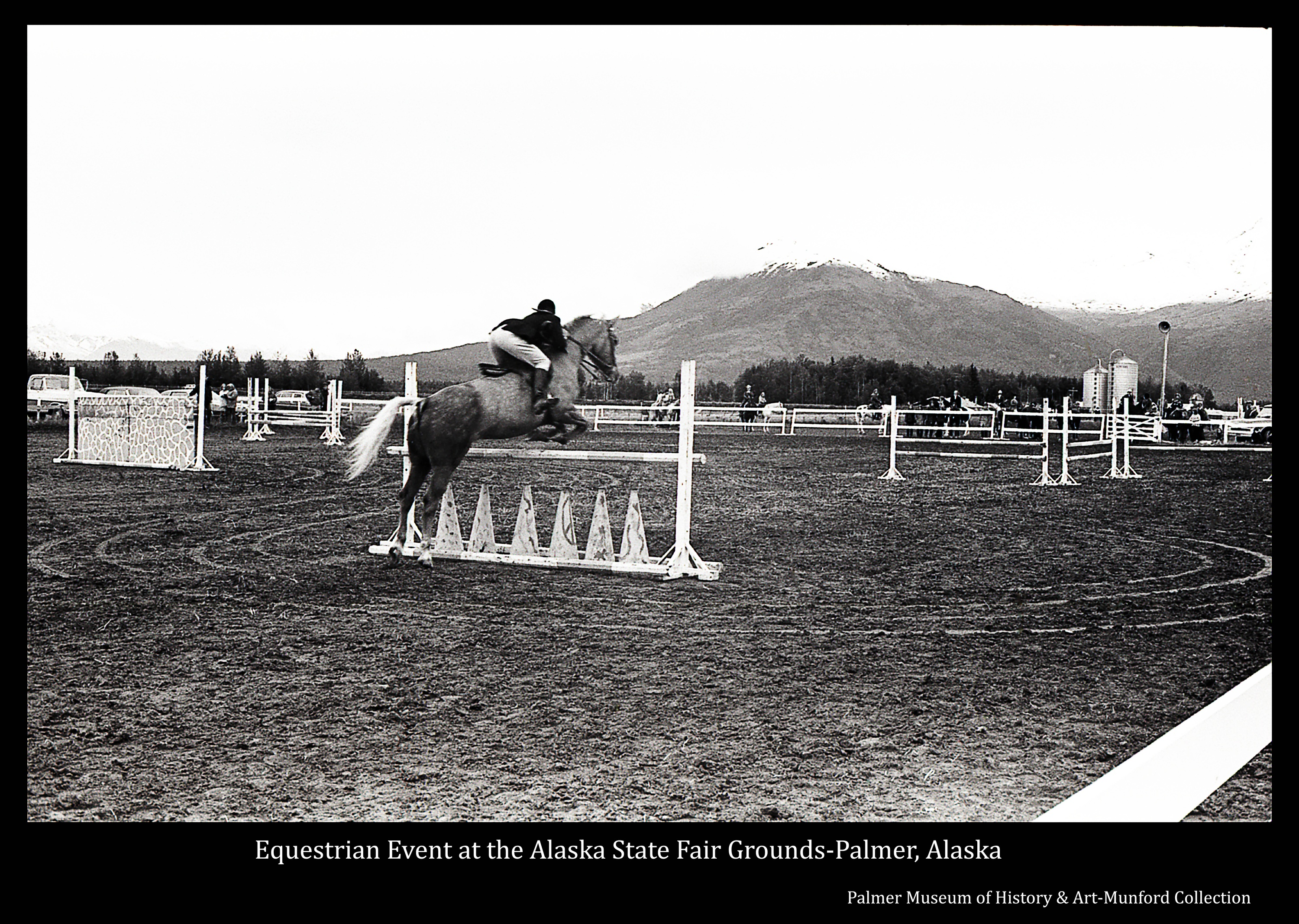 Image is of a horse and rider jumping a hurdle in the arena at the State Fairgrounds in Palmer.  People, horses and vehicles are evident outside the arena fence.  Chugach Mountains, capped with snow, are in background.