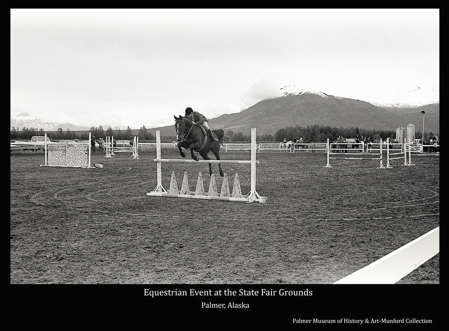 Image is of a horse and rider jumping over a hurdle bar at the State Fairgrounds in Palmer.  Other horses and riders are behind in middle ground.  Lazy Mountain, capped with snow, is in background.