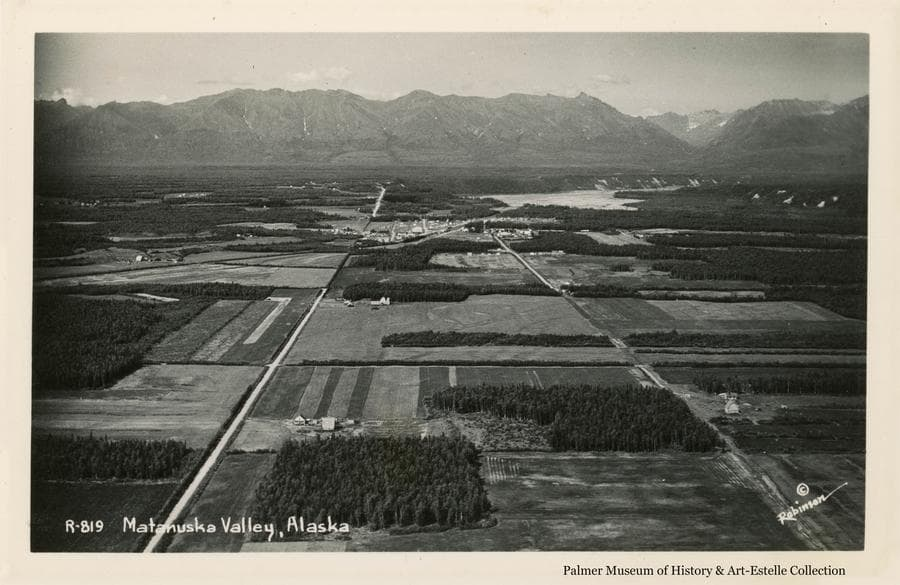 Image is a northerly low oblique aerial view across farm land south of Palmer, including the City of Palmer and the Matanuska River to the Talkeetna Mountains beyond.  Farms and forest clearing patterns, crop patterns and roads are apparent.