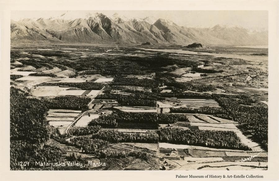 Image is an easterly low oblique aerial view across farm land southwest of Palmer, including Matanuska and the Matanuska Experiment Farm, across the Matanuska River to the mountains beyond.  Bodenburg Butte is visible.  Farms and forest clearing patterns, stump rows and roads are apparent.