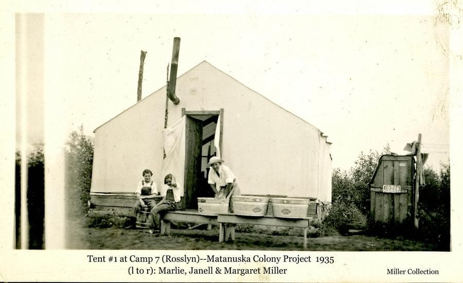 Image shows a woman, identified as Margret Miller, hand-washing clothes in wash tubs set up in front of their tent at Colonist Camp 7.  Two young girls, identified as Mardie and Janell Miller, sit nearby.  An outhouse and clothesline are evident at right