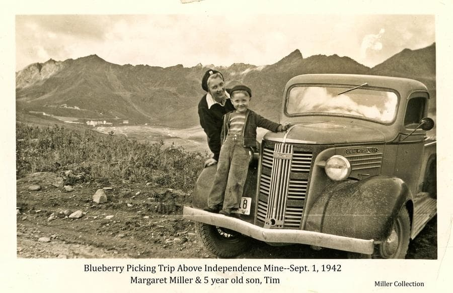Image shows Margaret Miller and her five year old son, Tim, perched on the front of a General Motors pickup truck in foreground.  Location is on the road over Hatcher Pass.  In background buildings of Independence Mine and Gold Chord Mine are visible.  Mountains form the far background.